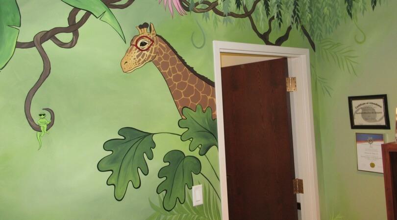Mural of a giraffe and a lizard wearing glasses in a jungle