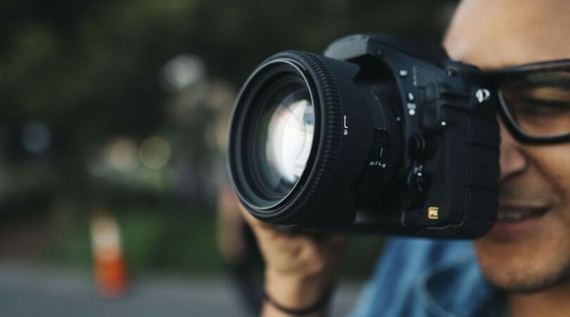 Man looking through camera lens wearing glasses